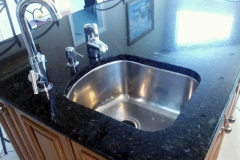 Granite countertop with new stainless steel sink. Black with light specs.