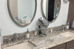 Bathroom vanity with twin oval mirrors.